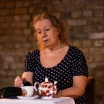 The actress Carrie Cohen looking sad in front of a pot of tea